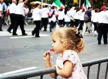 Una bambina sta guardando una parata Fotografie Stock