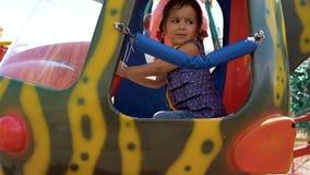Una bambina sta guidando un carosello stock footage