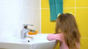 Una bambina sta lavando le sue mani stock footage