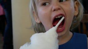 Una bambina sta mangiando l'ovatta dolce stock footage