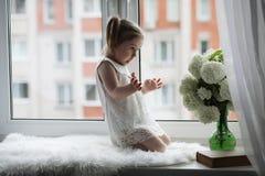 Una bambina sta sedendosi sul davanzale Un mazzo dei fiori Fotografie Stock Libere da Diritti