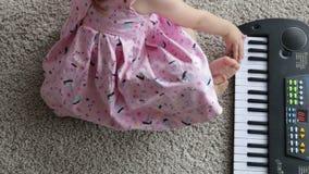 Una bambina sta sedendosi sul tappeto e sta giocando un giocattolo elettrico del piano Vista da sopra Video completo di HD video d archivio