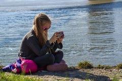 Una bambina sta sedendosi sulla banca del fiume con un telefono Un giorno di molla caldo fotografie stock libere da diritti