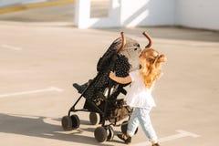 Una bambina sta spingendo la sua carrozzina Immagine Stock