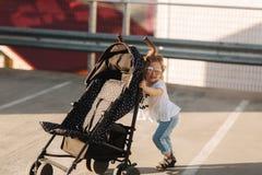Una bambina sta spingendo la sua carrozzina Fotografie Stock Libere da Diritti