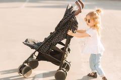 Una bambina sta spingendo la sua carrozzina Fotografia Stock Libera da Diritti
