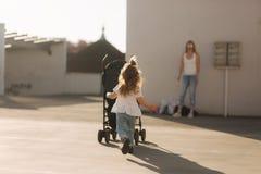 Una bambina sta spingendo la sua carrozzina Fotografie Stock