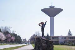 Una bambina sta stando vicino alla torre di acqua Il tempo di primavera? ? aumentato foglie, sfondo naturale Giorno pieno di sole fotografie stock libere da diritti