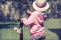 Una bambina sta tenendo un pattino e sta giocando fuori, ancora fotografie stock libere da diritti