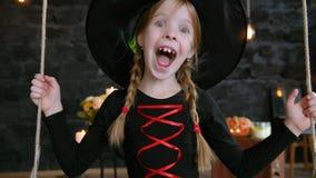 Una bambina, una strega, giro su un'oscillazione su Halloween archivi video