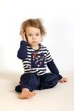 Una bambina studia un telefono. Fotografie Stock Libere da Diritti