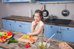 Una bambina sveglia assaggia il pepe bulgaro davanti ad una bella cucina fotografie stock