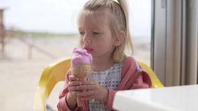 Una bambina sveglia gode di un cono gelato delizioso durante l'estate archivi video