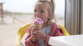 Una bambina sveglia gode di un cono gelato delizioso durante l'estate video d archivio