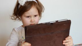 Una bambina sveglia sfoglia una lista musicale radiofonica sulla compressa, seleziona ed ascolta la canzone nelle cuffie Bambino  video d archivio