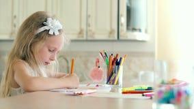 Una bambina sveglia si siede al suo scrittorio e disegna con le matite archivi video