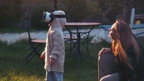 Una bambina sveglia usa un casco di realtà virtuale video d archivio