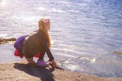 Una bambina tocca il fiume con la sua mano Una ragazza dal fiume un giorno soleggiato immagini stock