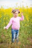 Una bambina in un campo del seme di ravizzone con un mazzo di camomille Fotografia Stock