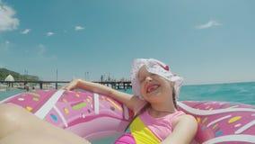 Una bambina in un cappello fresco ed in un bikini luminoso sta guidando su un cerchio e sta facendo un selfie, sorridente alla ma stock footage