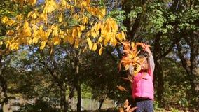 Una bambina in un rivestimento rosa la getta foglie su archivi video