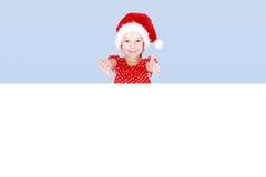 Una bambina in un vestito ed in un cappello rossi di Santa Claus mostra il suo dito sullo spazio dell'annuncio Immagini Stock