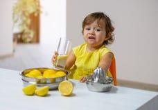 Una bambina in un vestito giallo assaggia la limonata cucinata immagini stock libere da diritti