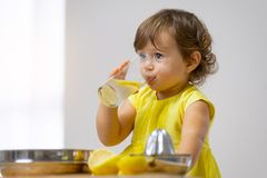 Una bambina in un vestito giallo assaggia la limonata cucinata fotografia stock