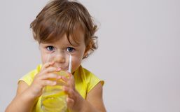 Una bambina in un vestito giallo assaggia la limonata cucinata fotografia stock libera da diritti