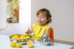 Una bambina in un vestito giallo assaggia la limonata cucinata fotografie stock