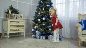 Una bambina in un vestito rosso sta ballando vicino ad un albero di Natale video d archivio