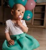 Una bambina in un vestito si siede sul pavimento con una tettarella, tiene un dito vicino alle sue labbra, silenzio, shhh quiet s immagini stock libere da diritti