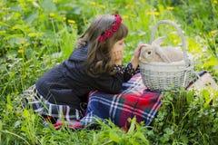 Una bambina in una corona osserva un coniglio in un canestro al tramonto in un parco Immagini Stock