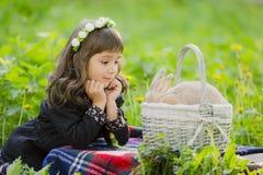 Una bambina in una corona osserva un coniglio in un canestro al tramonto in un parco Fotografia Stock Libera da Diritti