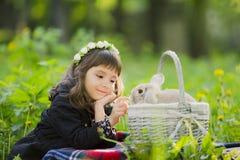 Una bambina in una corona osserva un coniglio in un canestro al tramonto in un parco Fotografia Stock