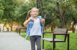 Una bambina va con uno zaino a scuola Il concetto di scuola, studio, istruzione, infanzia immagini stock