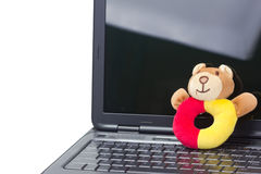 Una bambola sveglia che riposa sul computer portatile. Fotografia Stock Libera da Diritti