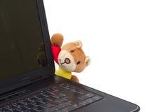 Una bambola sveglia che si nasconde al lato di un computer portatile. Fotografie Stock Libere da Diritti