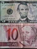una banconota brasiliana di 10 reais e banconota da cinque dollari, fondo e struttura americani Immagine Stock