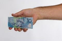 Una banconota da 10 dollari australiani in mano posteriore Fotografia Stock