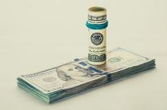 Una banconota in dollari arrotolata 100 che riposa su un altro ha inclinato la banconota in dollari 100 isolata su fondo bianco Fotografia Stock Libera da Diritti