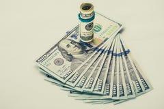 Una banconota in dollari arrotolata 100 che riposa su un altro ha inclinato la banconota in dollari 100 isolata su fondo bianco Immagini Stock