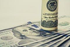 Una banconota in dollari arrotolata 100 che riposa su un altro ha inclinato la banconota in dollari 100 isolata su fondo bianco Immagine Stock