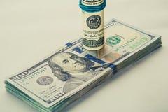 Una banconota in dollari arrotolata 100 che riposa su un altro ha inclinato la banconota in dollari 100 isolata su fondo bianco Fotografie Stock