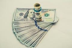 Una banconota in dollari arrotolata 100 che riposa su un altro ha inclinato la banconota in dollari 100 isolata su fondo bianco Immagine Stock Libera da Diritti