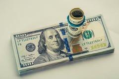 Una banconota in dollari arrotolata 100 che riposa su un altro ha inclinato la banconota in dollari 100 isolata su fondo bianco Fotografia Stock
