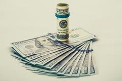 Una banconota in dollari arrotolata 100 che riposa su un altro ha inclinato la banconota in dollari 100 isolata su fondo bianco Immagini Stock Libere da Diritti