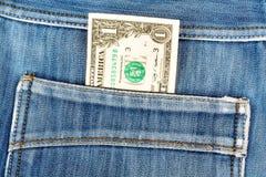 Una banconota in dollari che attacca nella tasca posteriore dei jeans del denim Fotografia Stock