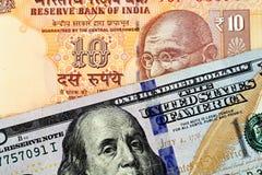 Una banconota indiana da dieci rupie con le cento banconote in dollari americana immagini stock libere da diritti