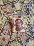 una banconota messicana e un fondo di 500 pesi con le banconote del dollaro Fotografie Stock
